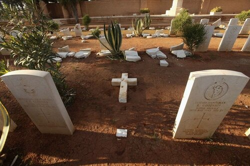 Grave stones and cross lie on ground in Benghazi Military Cemetery
