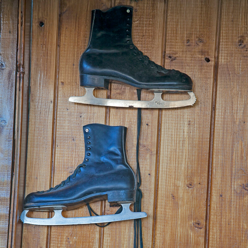 black skates hanging on a wooden wall