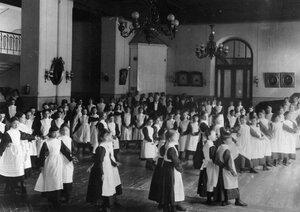 Учащиеся училища (младшая группа) за разучиванием танцев в танцевальном зале.
