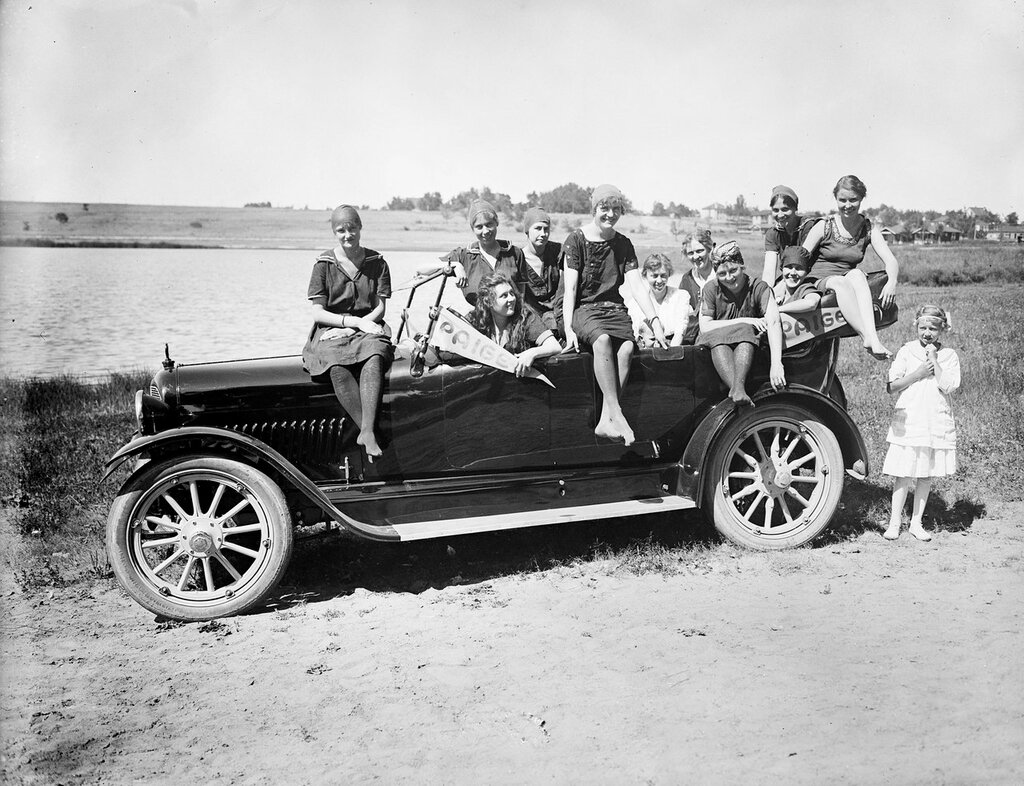 Bathing beauties. Several women in bathing suits and caps pose inside a convertible Paige-Detroit automobile for a dealership promotion in Denver, Colorado, probably Sloans Lake in background. 1916.