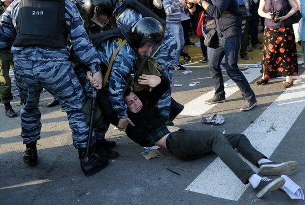 Russian Police officers detain an opposi