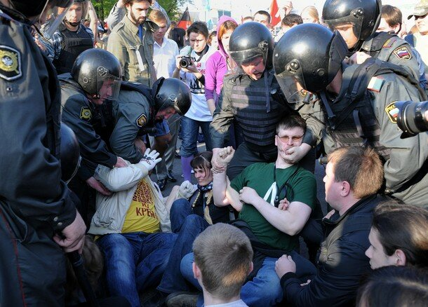 Russian Police officers detain oppositio