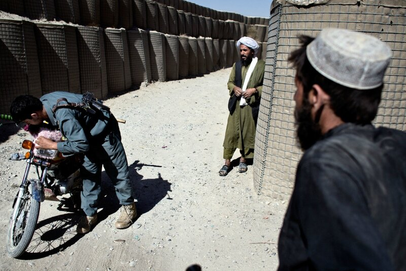 Afghanistan.<br />Afganske ANA-soldater i deres kvarterer, Gerehsk, Helmand.En bekymret mand får undersøgt sin motorcykel.