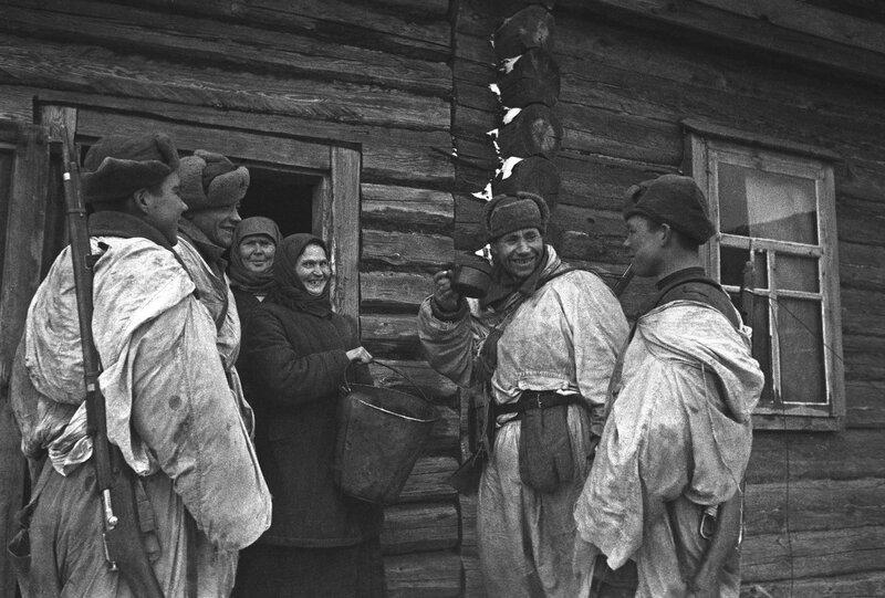 Крестьянка в освобожденном селе выносит солдатам ведро с водой во время Великой Отечественной войны.  Место: Россия.