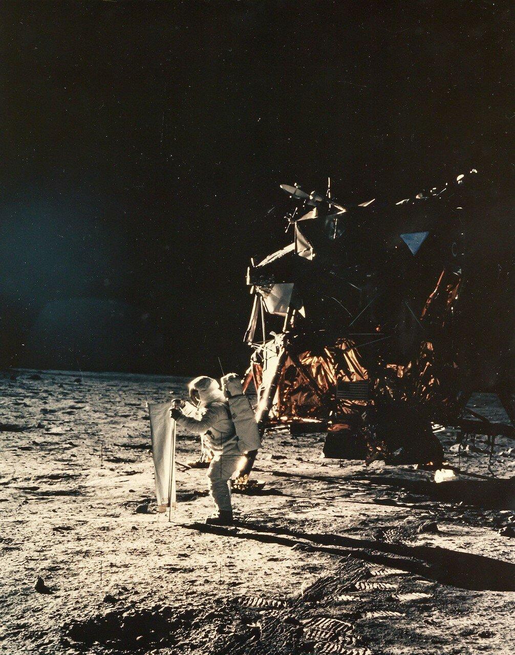 Через 15 минут после того, как Армстронг сделал первый шаг на Луне, из кабины начал спускаться и Олдрин. Армстронг, стоя внизу, недалеко от лестницы, корректировал его движения и фотографировал. На снимке: Первые фотографии человека, стоящего на поверхности Луны