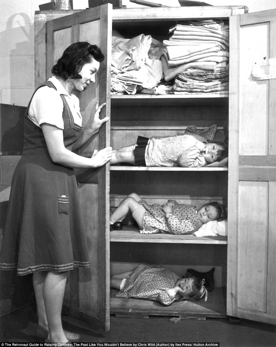 Женщина укрывает детей в шкафу во время немецкого авианалета на Лондон.