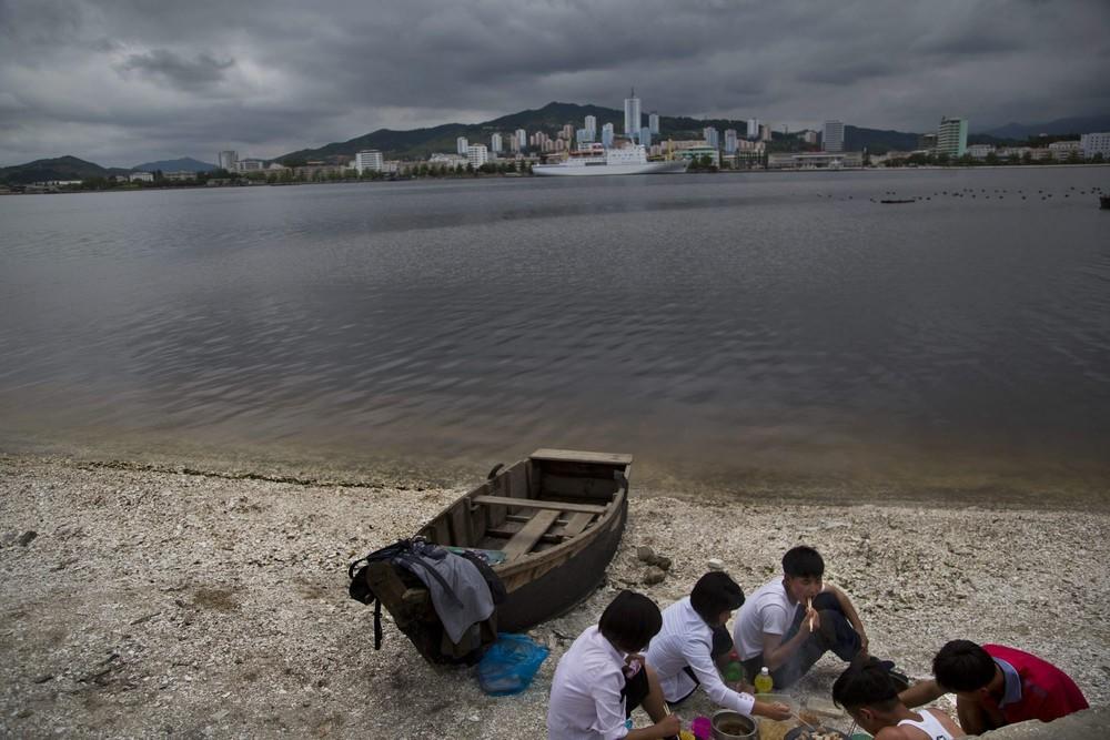 15. Группа молодых людей наслаждается пикником на пляже в Вонсане. (Photo by David Guttenfelder / AP