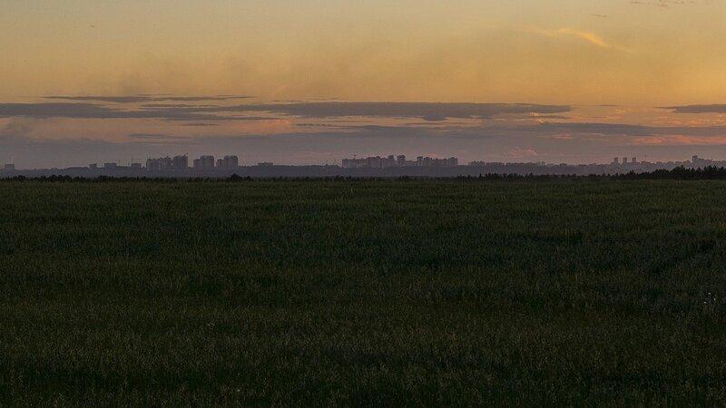 Вид с холма у деревни нижние Булдаки на закатный город Киров на горизонте: микрорайоны Солнечный Берег, Зональный, центр города