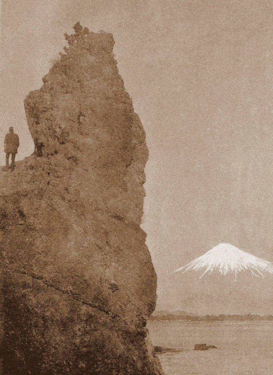 Человек на скале смотрит на заснеженную Фудзи
