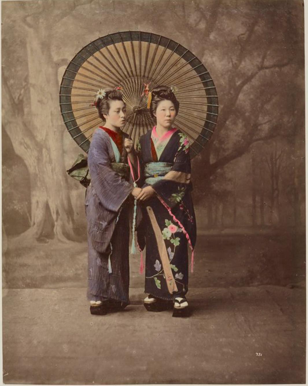 Две молодые девушки, несущие зонтик от солнца