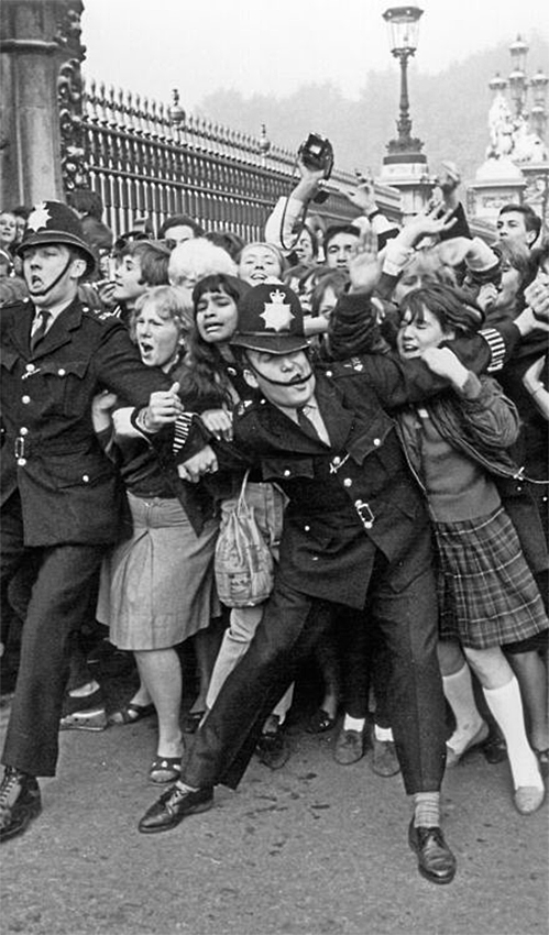 Police keeping back a crowd of young fans outside Buckingham Palace, London, as pop group the Beatles receive their MBEs.