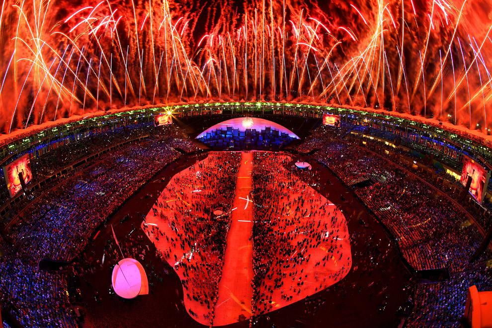 19. Местные контрасты. Жители смотрят церемонию открытия по ТВ. (Фото Ricardo Moraes | Reuters)