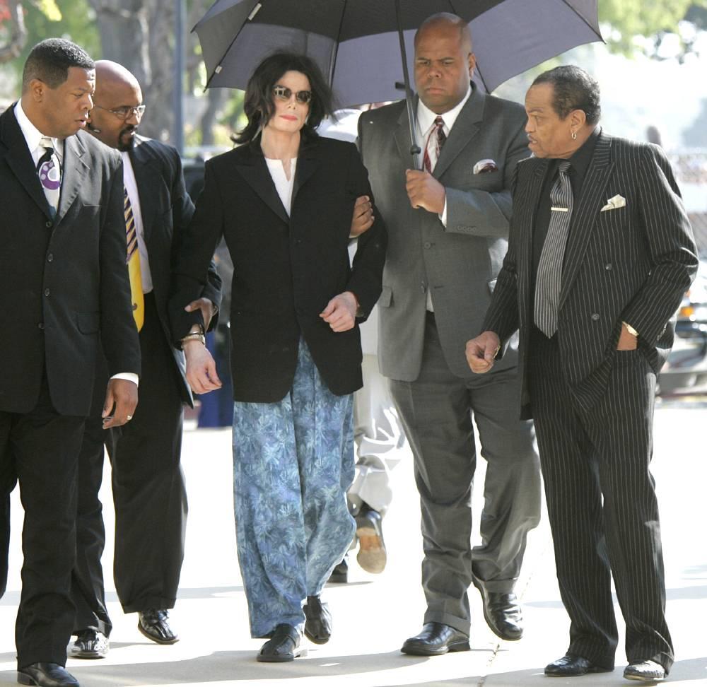 Майкл Джексон в пижамных штанах идет в сопровождении телохранителей на заседание суда 10 марта 2005