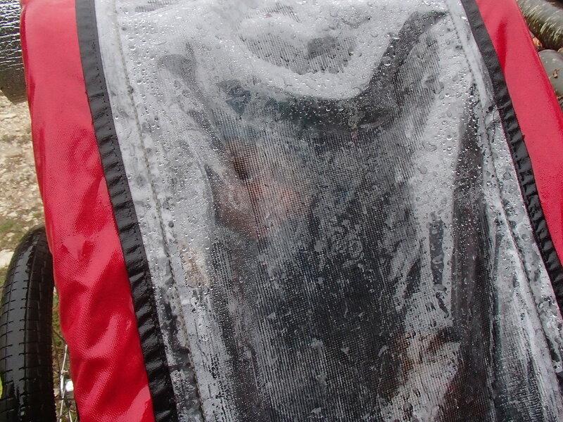 ребенок в запотевшем вело-прицепе thule под дождем