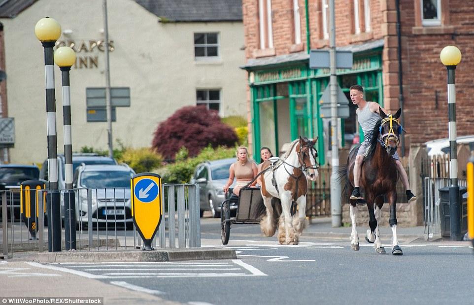 Юноша скачет на лошади по главной улице Эпплби, две девушки на двуколке следуют за ним.