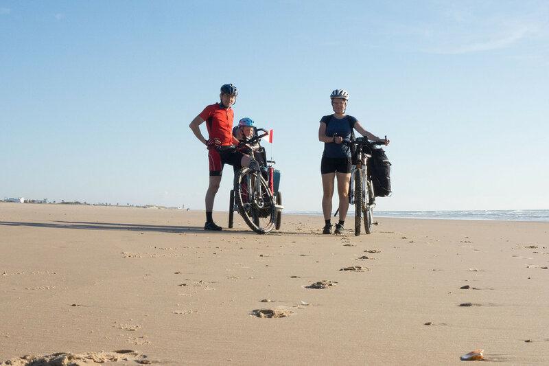 семья с ребенком в велопоходе на пляже атлантического океана