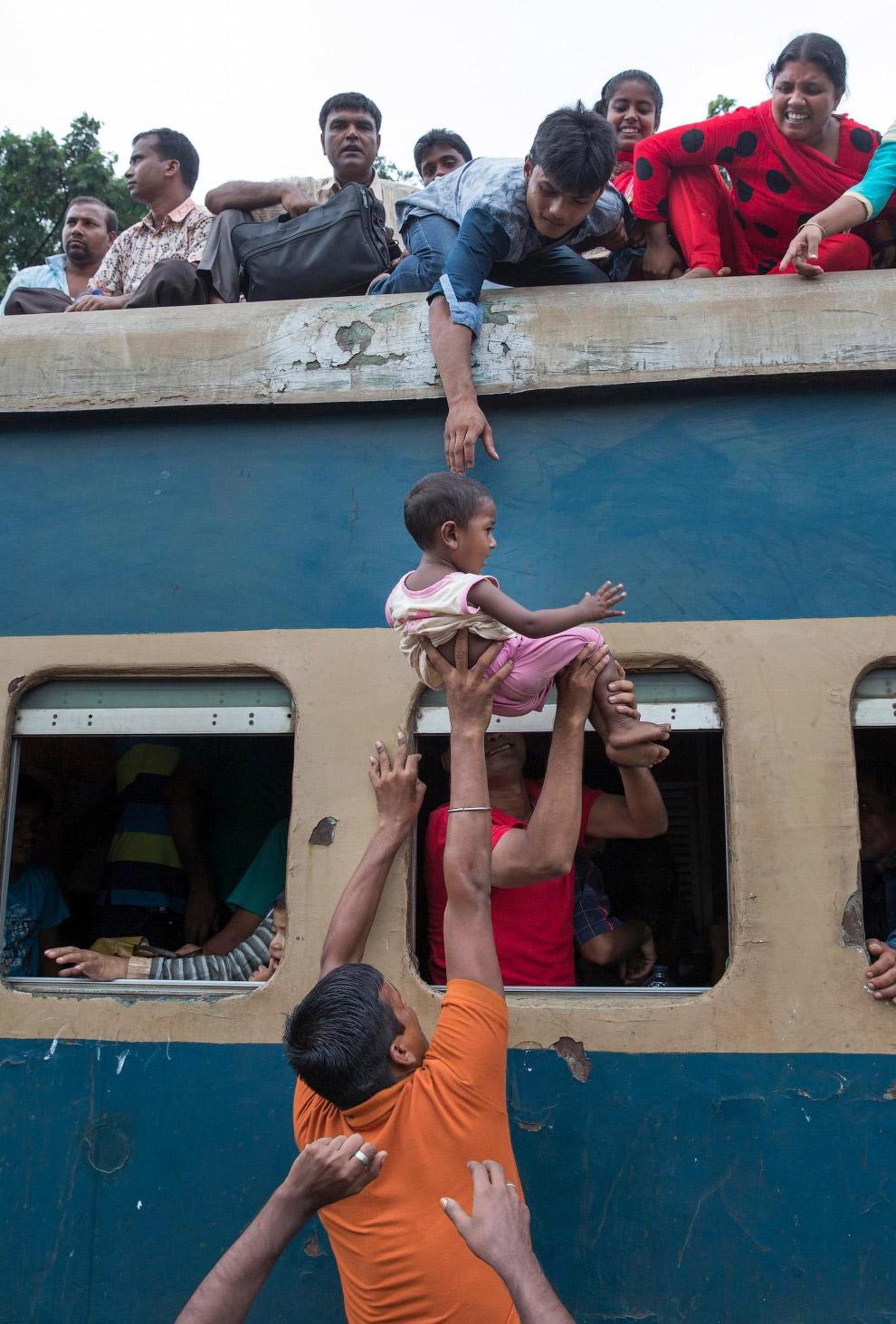 5. Те, кто не влез во внутрь и на крышу пытаются ехать в висячем положении. (Фото Yousuf Tushar