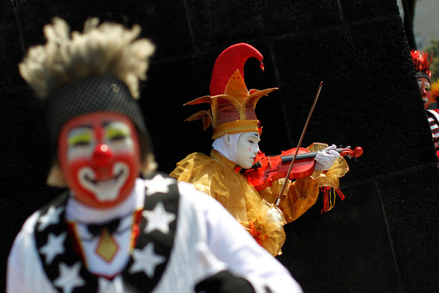 A clown plays the violin during the XXI Convention of Clowns, at the Jimenez Rueda Theatre, in Mexic