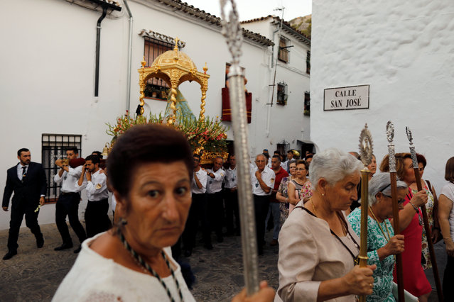 Members of the Virgin of los Angeles brotherhood take part during a procession in the white village