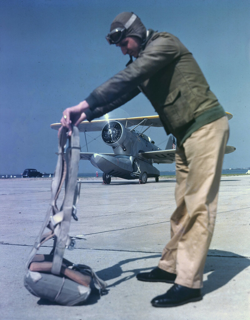Pilot shaking out his parachute in front of a U. S. Coast Guard Grumman JF-2 Duck with engines running, probably Floyd Bennett Field, N.Y. ca. 1940.