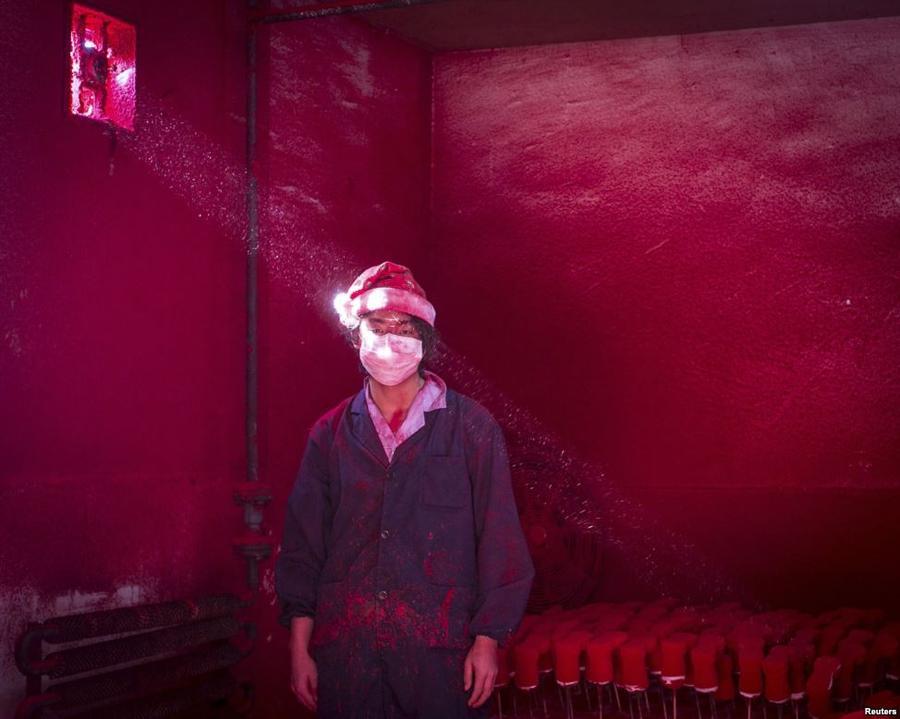 10. Китайский рабочий завода по производству елочных игрушек, в помещении, где сушат краску на новог