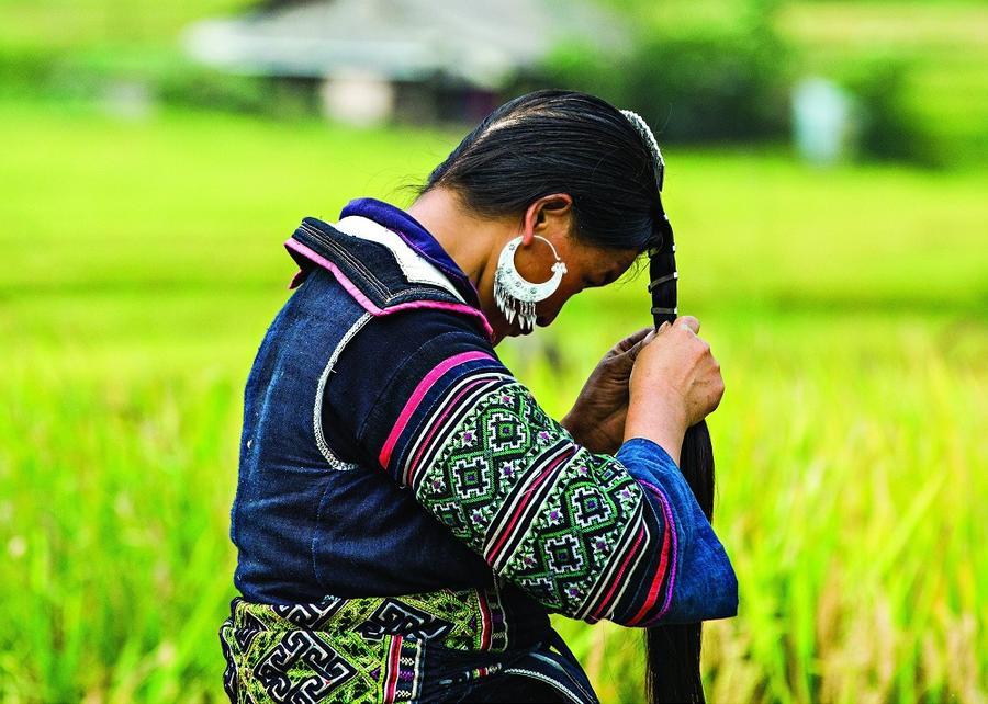1. Женщина племени дао — в красной шляпе, с крашенной индиго рукой — она делала традиционный костюм.