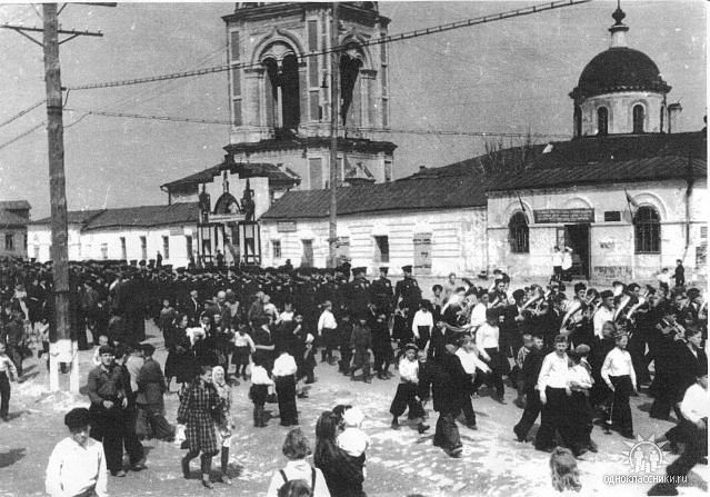 Праздник 1 мая. Парад на Советской. Вокруг церкви постройки не сохранились. Ворота были бело-синими, как здание библиотеки. Снесены в 60-70е. Здесь было кафе, фотоателье. Со стороны дороги к милиции был рынок.