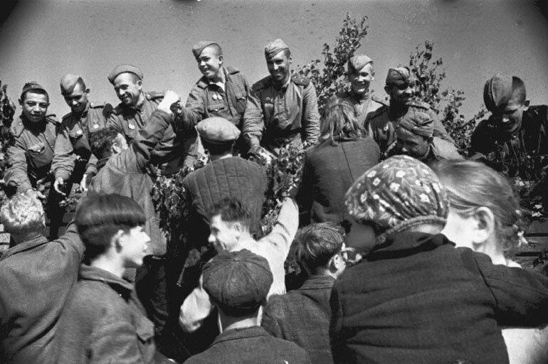 Население освобожденных районов Латвии встречает воинов Красной Армии. 1944 год.   Место съемки: 2-й Прибалтийский фронт   Автор съемки: В. Гребнев