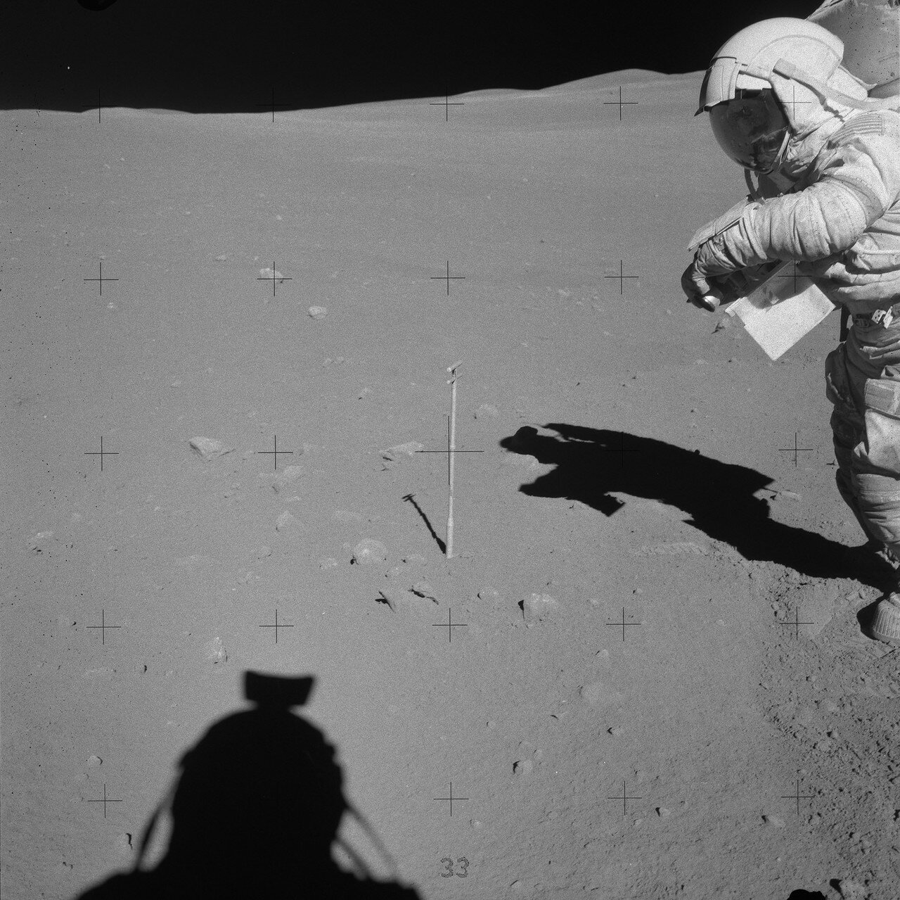 Очередную остановку (Station 6) астронавты сделали у 10-метрового кратера у подножия горы Стоун Маунтин, где геологи надеялись получить образцы формации Кэйли. На снимке: Джон Янг и Чарли Дьюк (внизу тень от его гермошлема) перед сбором первого образца
