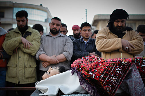 Men say prayers near the body of a man killed during clashes