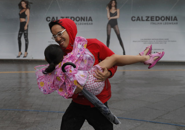A man carries a girl brave the wind on the waterfront of Victoria Habour as Typhoon Haima approaches
