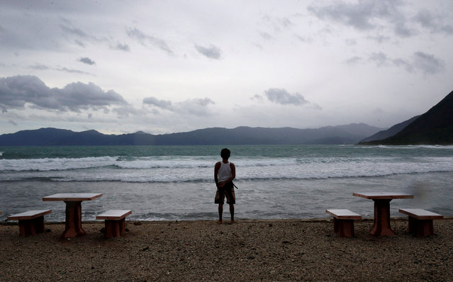 A resort worker looks out at a beach at an empty resort as Typhoon Haima strikes Pagudpud, Ilocos No