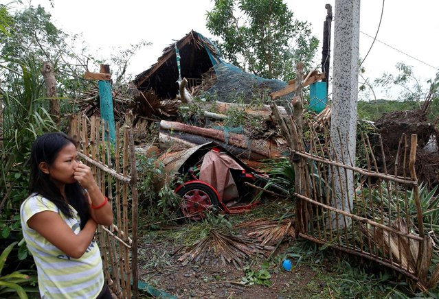 A woman stands outside her house which was damaged by a fallen tree during Typhoon Haima, in Bangui,