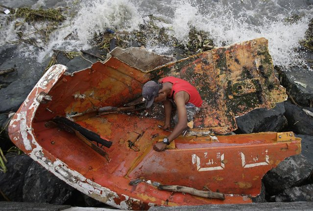 Filipino Joybin Marayo, 58, salvages metals on a damaged boat that was washed ashore by strong waves
