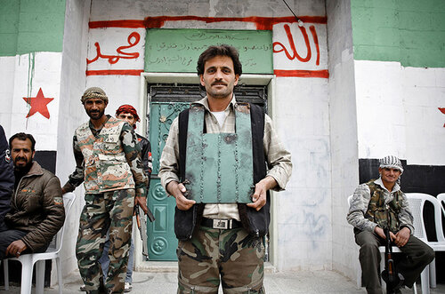 A rebel of the Free Syrian Army shows off his home-made body armour