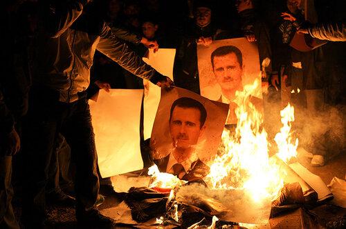 Young men burn posters of Bashr al-Assad during a night demonstration