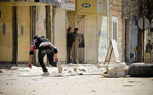 A rebel of the Free Syrian Army runs after placing an IED in the road