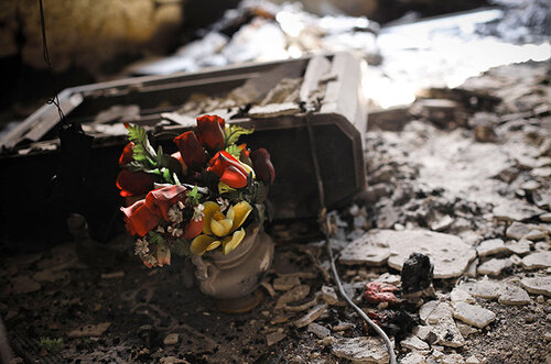 Plastic flowers lie amongst the burned ruins of a house