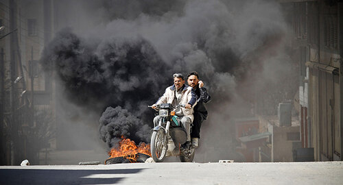 Citizens of Saraquib City flee the town on motorcycle while car tyres burn