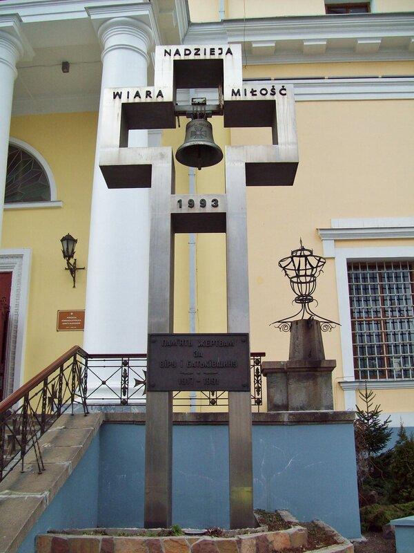 Крест-колокол перед входом в костел