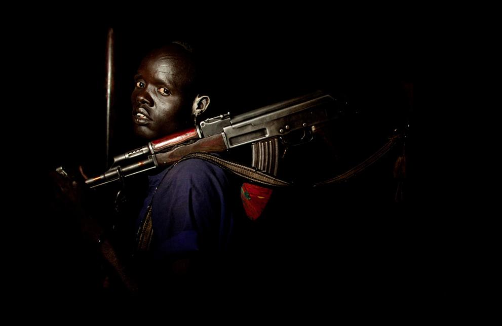30. Молодой охранник пастбищ племени динка в округе Вунлит. Он держит автомат АК-47 – обычное оружие