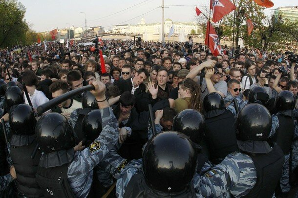 Russian riot police scuffle with protestors during the