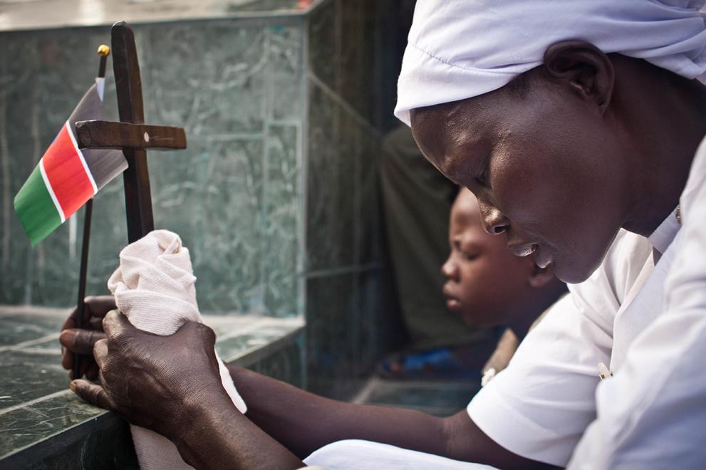 24. Женщина с флагом Южного Судана и крестом молится у основания статуи Джона Гаранга де Мабиора. (A
