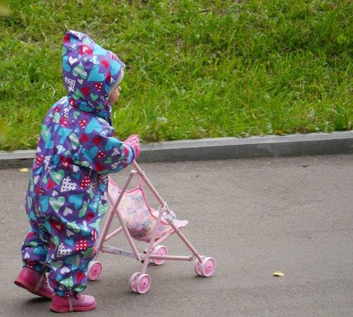 Малышка гуляет с кукольной коляской