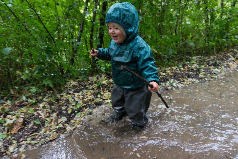ребенок в походе бегает по лужам под дождем