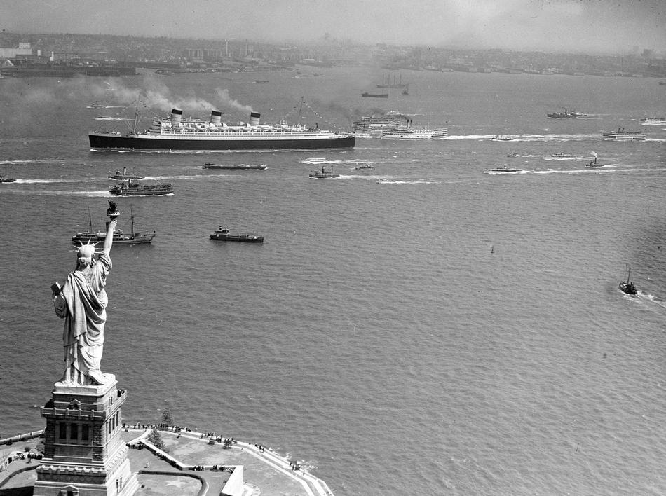 13. Океанский лайнер Queen Mary проходит мимо статуи Свободы в бухту Нью-Йорка во время первого рейс