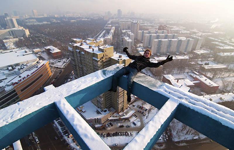 1. Макс Полатов балансирует над Москвой на высоте в 130 метров, зацепившись ногой за балку. Повиснув