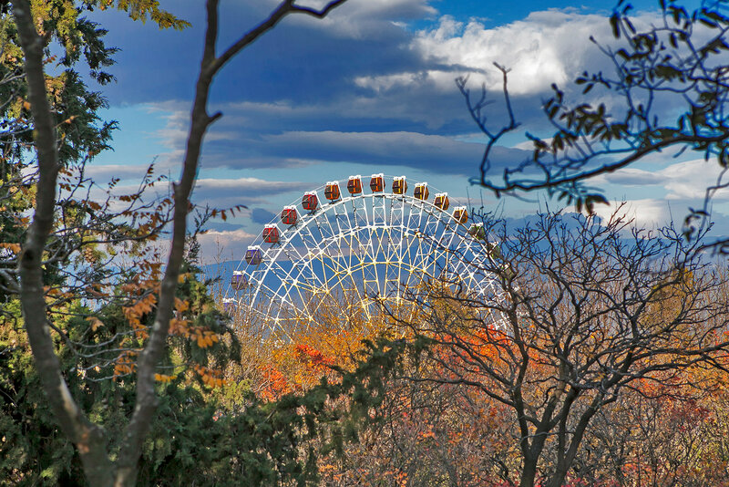 Ferris wheel in Tbilisi on bright blue sky background