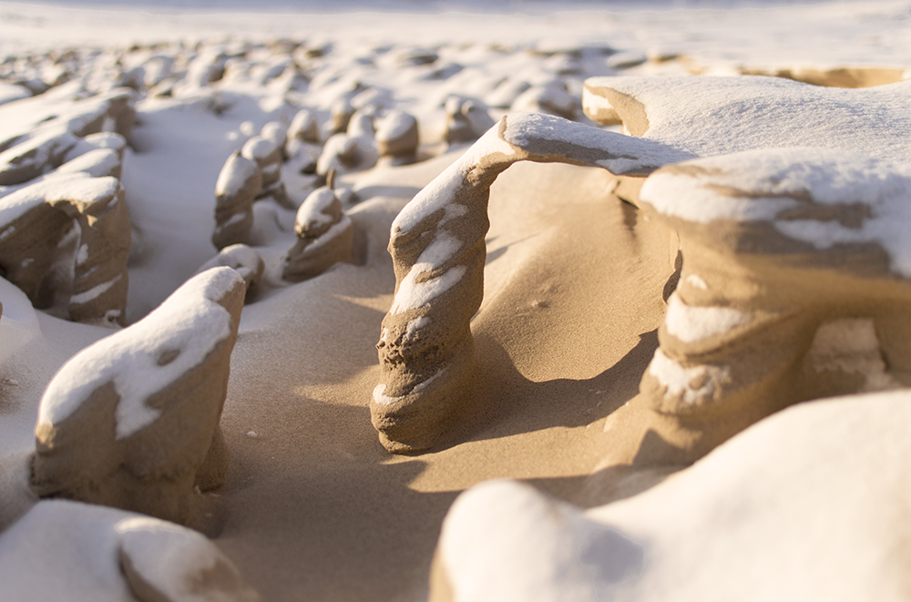 Strong Winds Carve Otherworldly Towers from Frozen Sand on the Shore of Lake Michigan