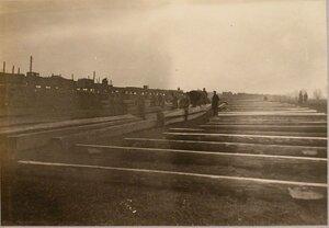 Солдаты укладывают по номерам прогоны и поперечины на берегу.